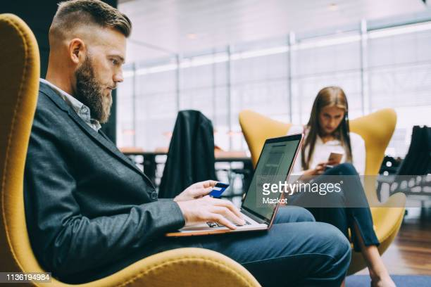 side view of businessman holding credit card while using laptop at airport - surfing the net stock pictures, royalty-free photos & images