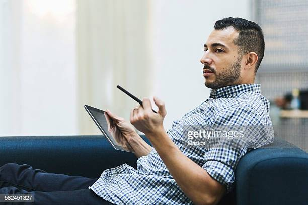 side view of businessman holding digital tablet while relaxing on sofa at office - homme maghrebin photos et images de collection