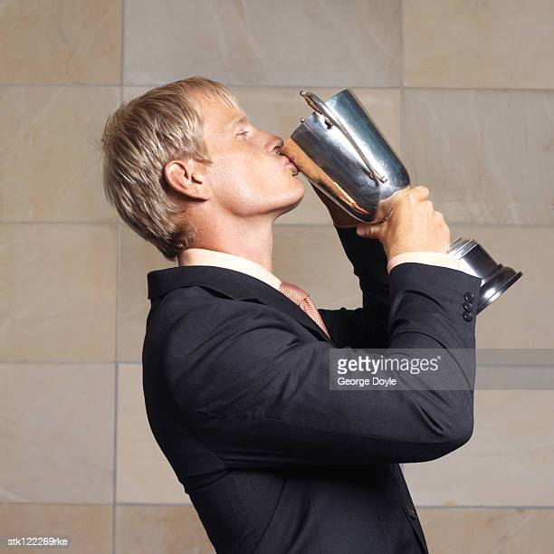 side view of businessman kissing trophy