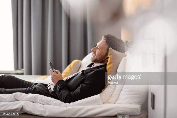 side view of businessman listening to music while lying on bed at hotel room - hóspede - fotografias e filmes do acervo