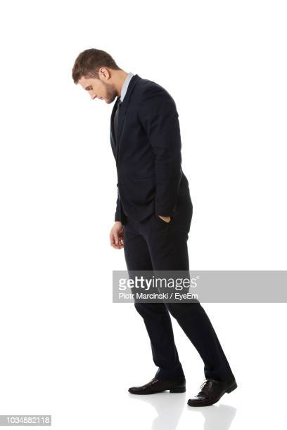 side view of businessman looking down while standing against white background - guardare verso il basso foto e immagini stock
