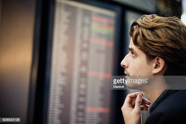 Side view of businessman reading arrival departure board at airport