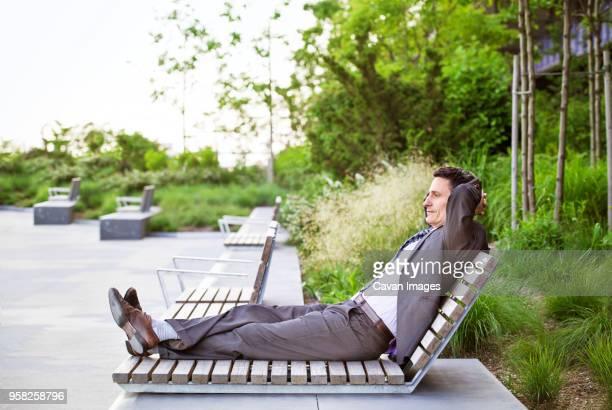 side view of businessman relaxing on lounge chair - nur erwachsene stock-fotos und bilder