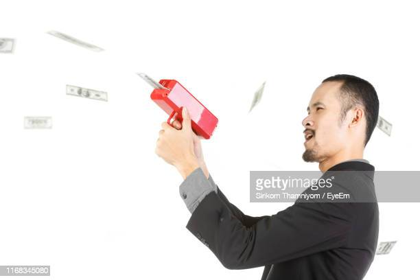 side view of businessman removing paper currency from machinery against white background - vuurwapen stockfoto's en -beelden