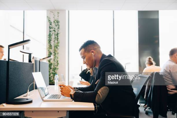 Side view of businessman sitting at desk listening to in-ear headphones while using smart phone in office