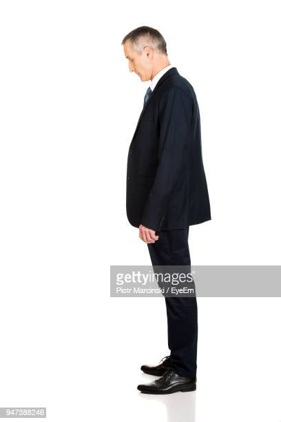 side view of businessman standing against white background - 下を向く ストックフォトと画像