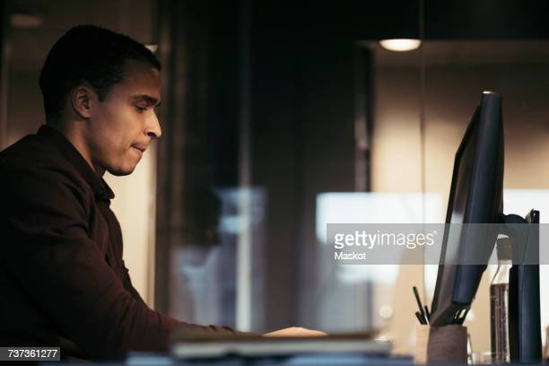 Side view of businessman using computer at desk in dark office