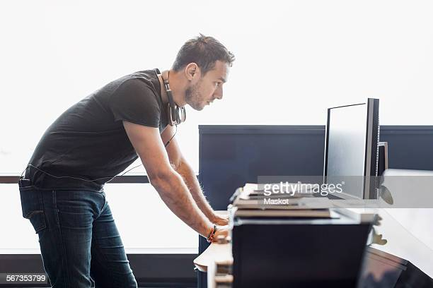 Side view of businessman using computer at desk in office