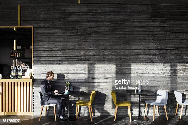 Side view of businessman using laptop while sitting at table