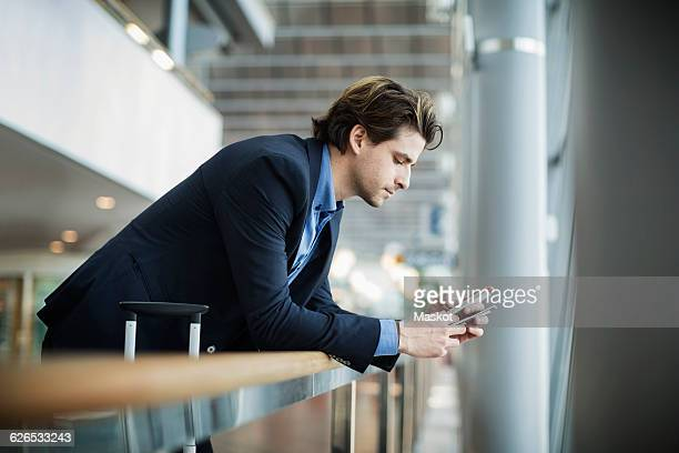 Side view of businessman using mobile phone while leaning on railing at airport
