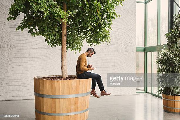 side view of businessman using mobile phone while sitting on pot in creative office - assis photos et images de collection