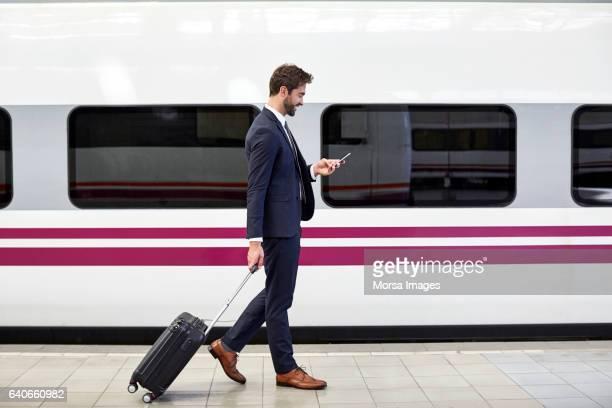 vista lateral do empresário usando telefone na estação - plataforma de estação de trem - fotografias e filmes do acervo