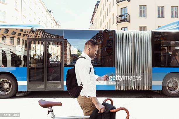 Side view of businessman using smart phone while standing with bicycle against bus on street