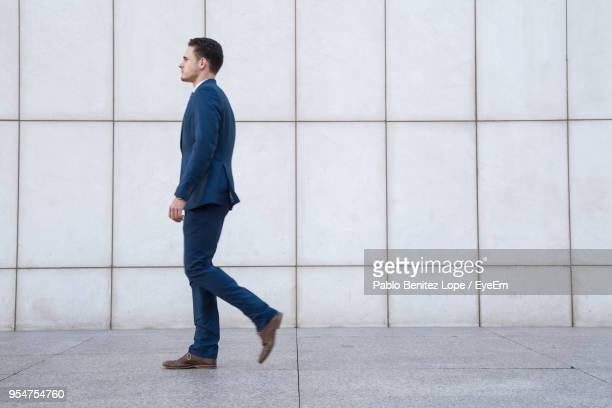 side view of businessman walking on footpath - van de zijkant stockfoto's en -beelden