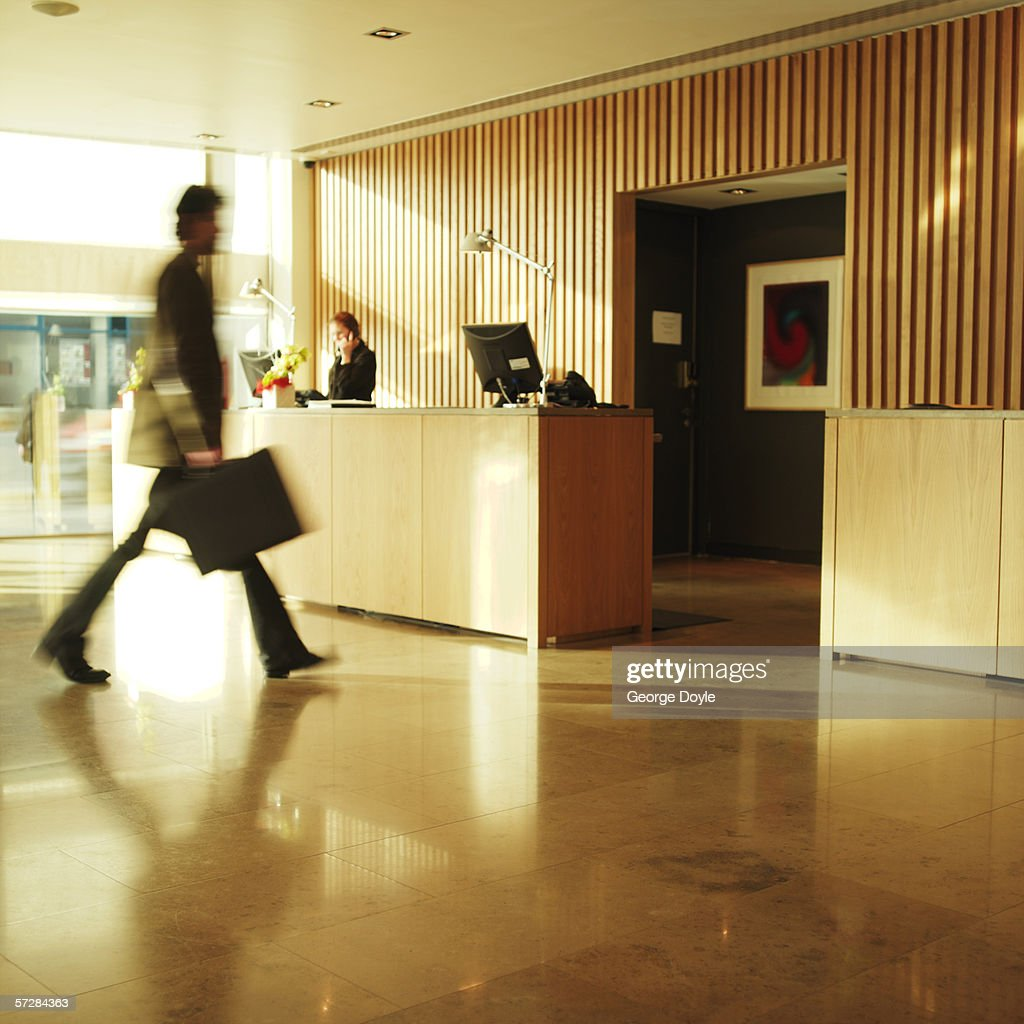 Side view of businessman walking past hotel reception : Stock Photo