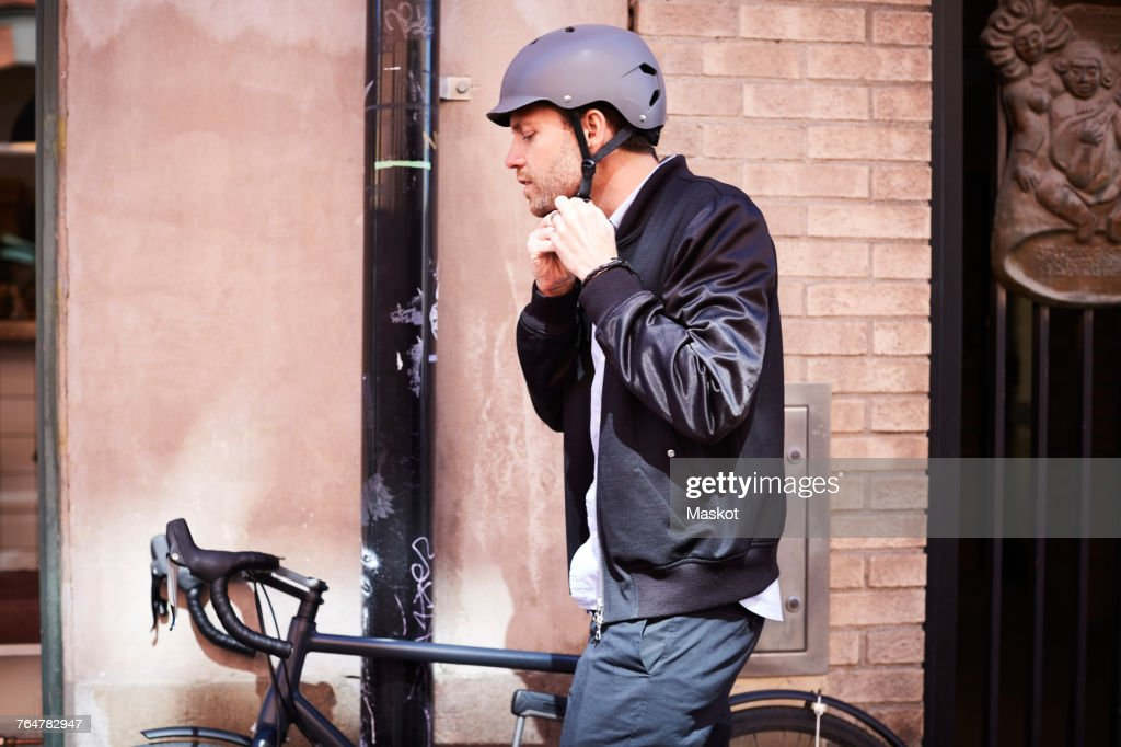 Side view of businessman wearing helmet while sitting on bicycle by wall at city : Stock Photo