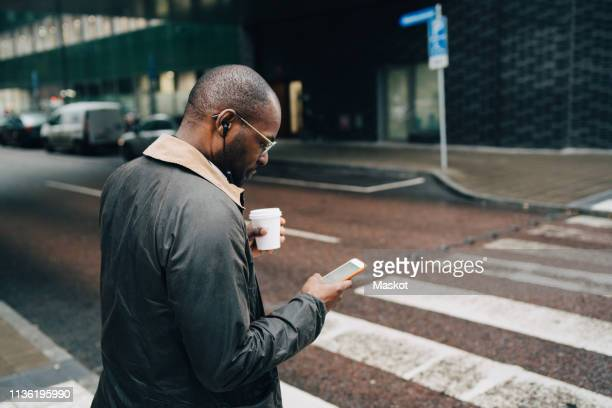 side view of businessman with coffee using mobile phone while crossing road in city - commuter stock pictures, royalty-free photos & images