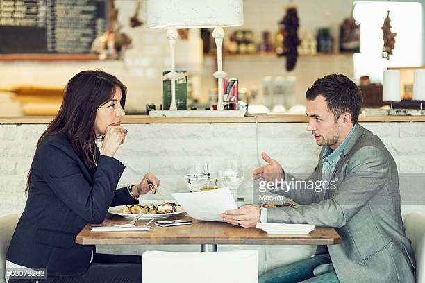 Side view of businessman with female colleague discussing paperwork at restaurant table