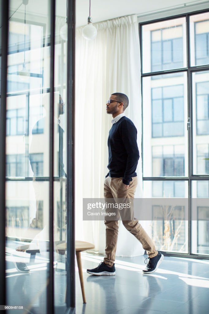 Side view of businessman with hands in pockets walking at office corridor : Stock Photo