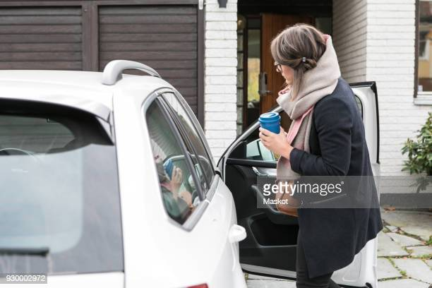 side view of businesswoman entering into car on street - entering stock pictures, royalty-free photos & images