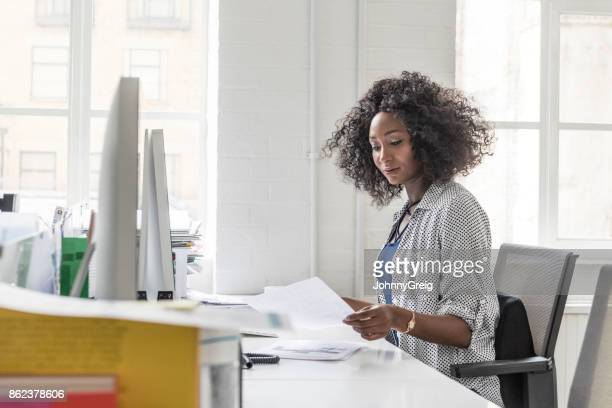 side view of businesswoman holding letter and sitting at desk - black blouse stock pictures, royalty-free photos & images