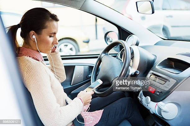 Side view of businesswoman listening music through smart phone while driving car
