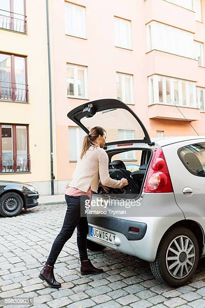Side view of businesswoman loading luggage in car trunk on street