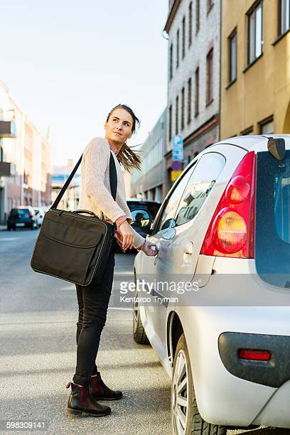 Side view of businesswoman opening car door on street