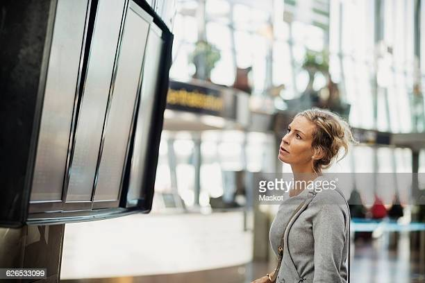 Side view of businesswoman reading arrival departure board at airport