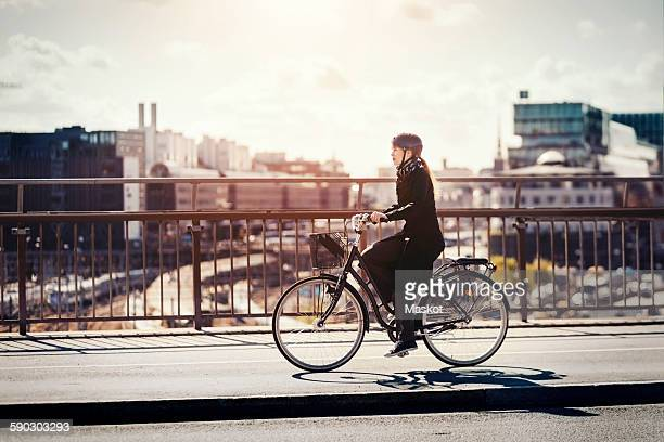 Side view of businesswoman riding bicycle on bridge in city
