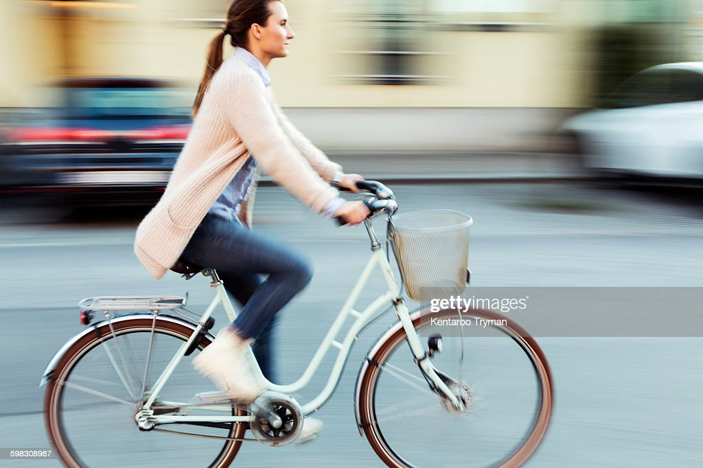 Side view of businesswoman riding bicycle on road : Stock Photo