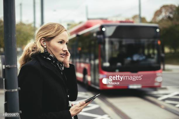 Side view of businesswoman talking on mobile phone with bus in background