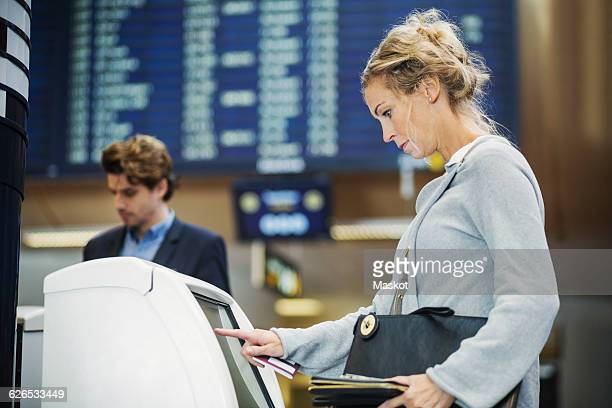 Side view of businesswoman using check in machine at airport