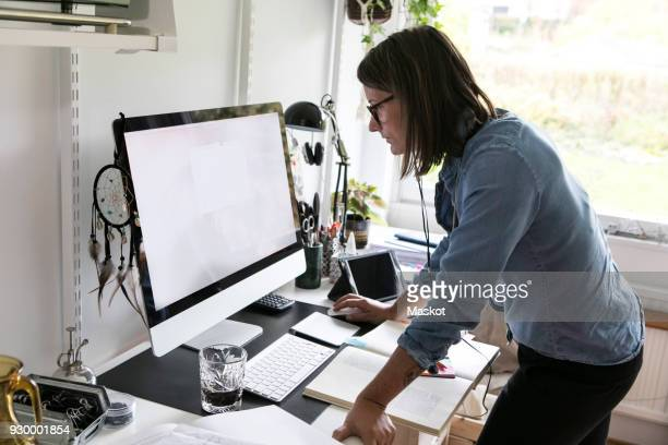 side view of businesswoman using computer while standing at home - home icon stock photos and pictures