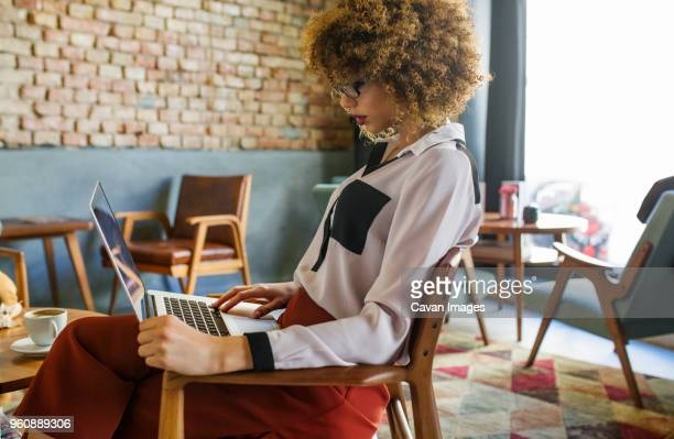side view of businesswoman using laptop in hotel lobby - cheveux naturels photos et images de collection