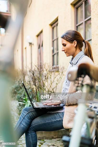 Side view of businesswoman using laptop on sidewalk