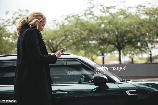 Side view of businesswoman using mobile phone by car