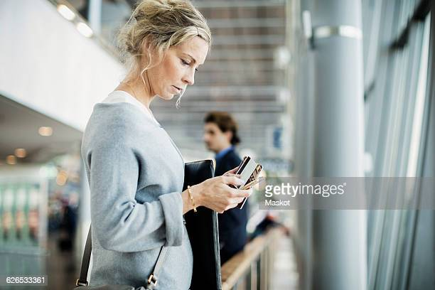Side view of businesswoman using smart phone at airport