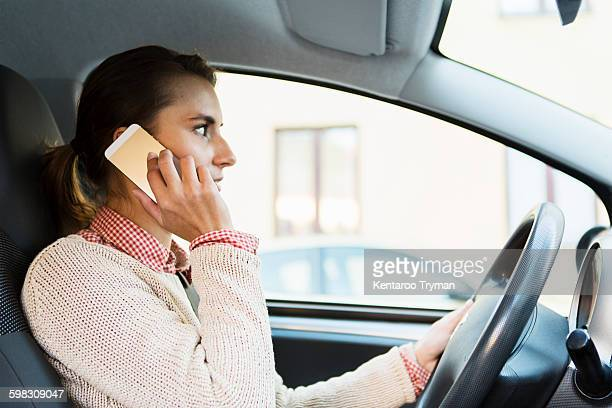Side view of businesswoman using smart phone while driving car