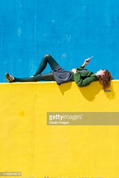 side view of businesswoman using smart phone while lying on yellow wall during sunny day - lying down ストックフォトと画像