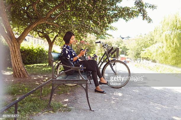 Side view of businesswoman using smart phone while sitting on park bench