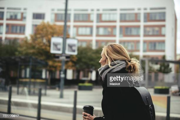 side view of businesswoman wearing winter coat at tram station - coat ストックフォトと画像