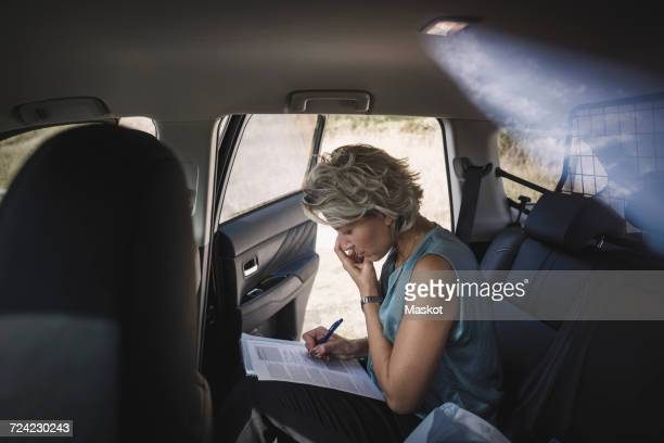 Side view of businesswoman writing on document car