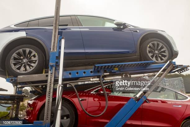 Side view of car carrying truck delivering new Tesla Motors automobiles on the 680 Freeway in the San Francisco Bay Area Danville California August...