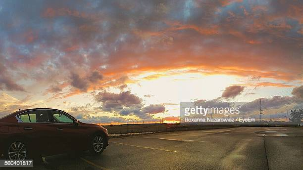 Side View Of Car On Road Against Scenic Sky