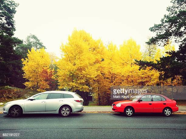 side view of cars by autumn trees against sky - seitenansicht stock-fotos und bilder