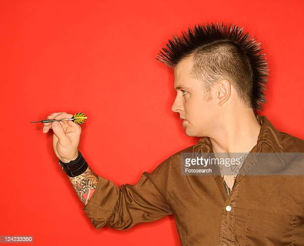 Side view of Caucasian man with mohawk holding dart against red background.