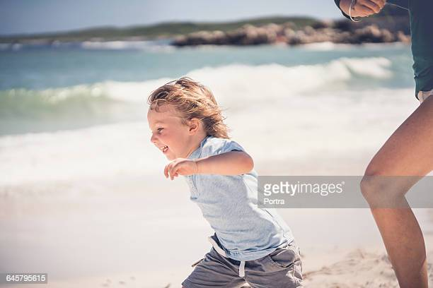 Side view of cheerful boy running at beach