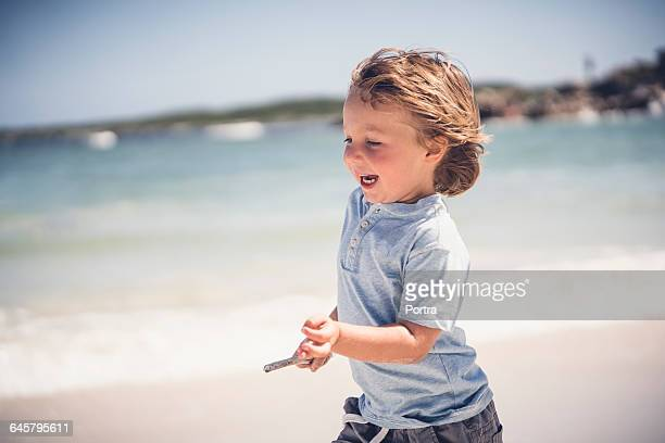Side view of cheerful boy running on shore