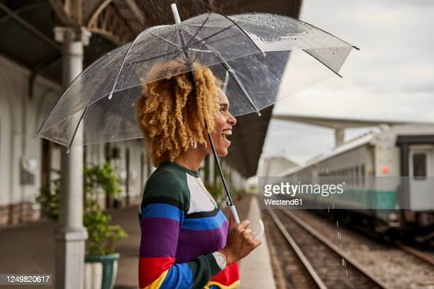 side view of cheerful young woman enjoying while standing with umbrella at railroad station during monsoon - paraplu stockfoto's en -beelden